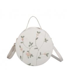 Malá dámská kulatá kabelka zdobená drobnými květinami
